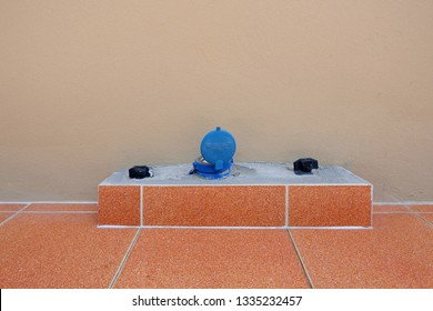 Blue water meter and black ball valves on orange floor tiles with brown painted concrete wall background, water supply system installation of home
