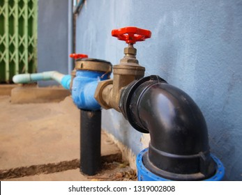 Blue water meter and valve: installed beside the gray wall for measuring volume and calculating water volume and sending values to the top dial. On the floor and cement wall.selective focus