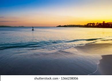 Blue water on Silgar beach in Sanxenxo tourist city at golden dusk