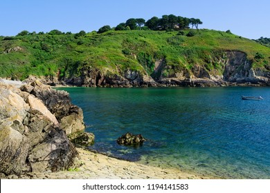Blue water and rugged cliffs in Saints Bay Harbour, Guernsey.