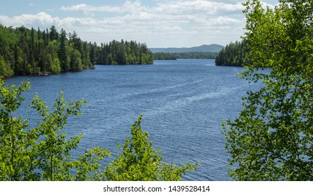 Blue water scene through trees in Fjord National Park in Saguenay Region of Quebec Canada