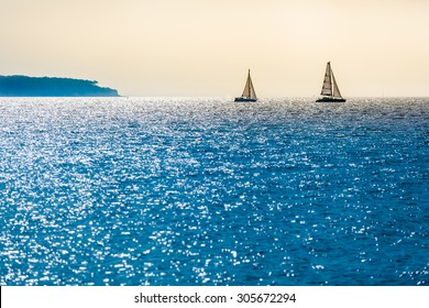 Blue water of the sea and two small boats sailing into the evening sky/Two Sailboats at the Horizon