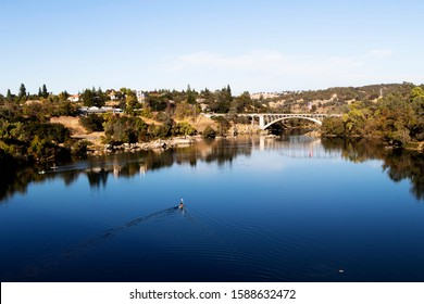 Blue Water And Sky Lake Natoma And Rainbow Bridge Folsom California With Trees Reflected In Water People Paddling