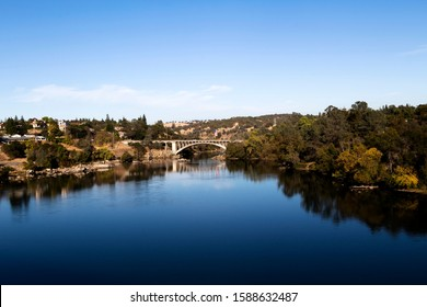 Blue Water And Sky Lake Natoma And Rainbow Bridge Folsom California With Trees Reflected In Water