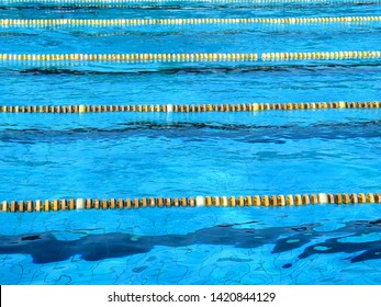 Blue water surface of swimming pool with yellow and white stripe separator. Swimming lanes in the pool. Sport poster concept background design.