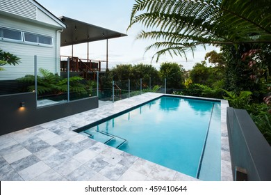 Blue water swimming pool with floor tiles under green trees close up with a garden including a bunch of green leaves, there is a house or hotel from the side at evening or morning sky