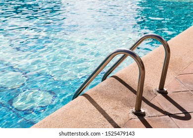 Blue water of swimming pool and Grab bars ladder, swimming pool ladder, sunshine