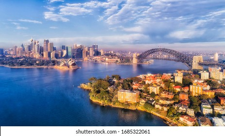 BLue water of Sydney harbour with major city landmarks on waterfront of CBD and north shore in aerial view.