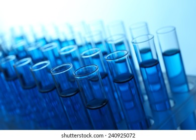 Blue water in a transparent test-tube on light background