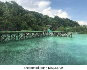 Blue watercolor beach with a wooden bridge in Baer Island, Kei Island, Indonesia