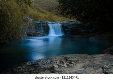 Blue waterfall cascade in the beautiful brazilian rainforest between rocks and trees
