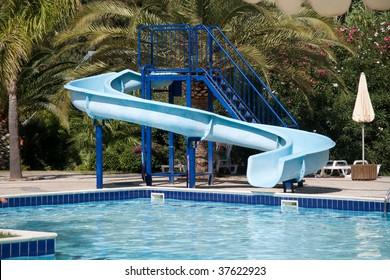 Blue waterslide ending in a swimming pool