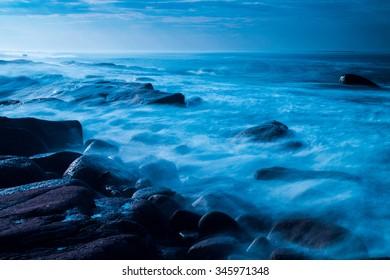 Blue wave breaking on shore