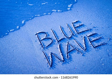 'BLUE WAVE' written in the sand on the beach with the sea washing up the shore. Shot with blue lens filter to enhance color.