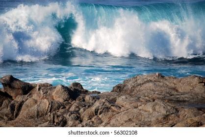 Blue waves crashing near a rocky shore