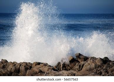 Blue waves crashing on a rocky shore