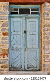Blue weathered front door of an old stone house at south Pelion, Greece