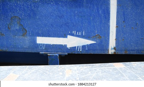 Blue weathered urban street wall surface with spray pained stencil arrow