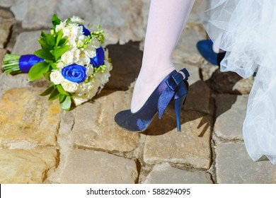 blue wedding shoe  near blue and white wedding bouquet with roses