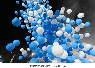 blue and white balloons flying up in the dark sky