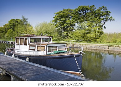 A blue and white boat on the Forth and Clyde Canal near the Falkirk Wheel in Central Scotland, UK.