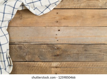 Blue and white checkered dishcloth on brown rustic wooden plank table flat lay top view from above with copy space