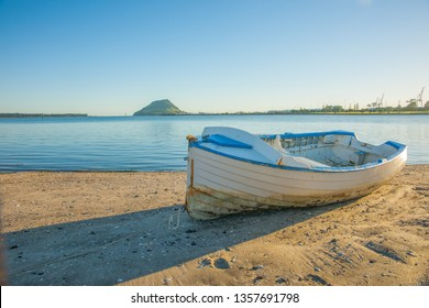 Blue and white clinker dinghy on Tauranga harbour beach with blue harbor and landmark Mount Maunganui in distance.