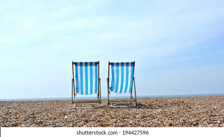 Blue and white deck chairs facing out to sea.