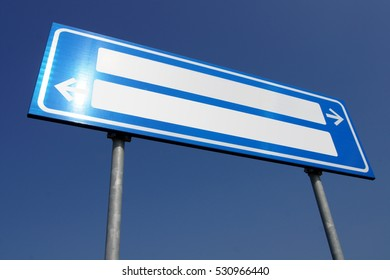 A blue and white directional road sign with empty tag space. Two arrows pointing in two opposite directions