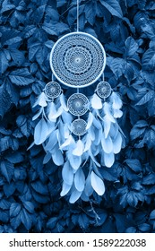 Blue and white Dreamcatcher made of feathers leather beads and ropes in classic blue trendy color, hanging. background. Color of the year 2020