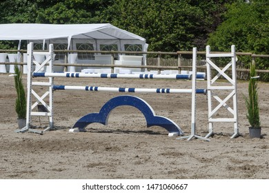 Blue and white fence for horse jumping
