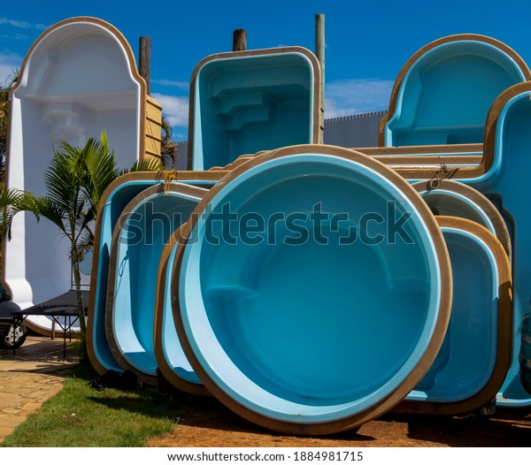 blue and white fiberglass pools on display for sale
