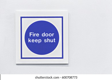 Blue and white fire door safety sign on a white background.