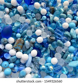 Blue and white glass beads for jewelry making on white background. Hobby, handmade jewelry, craft. Beads background.