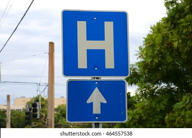 Blue and White Hospital Sign H Symbol Straight Ahead Arrow Pointing Up with Cloudy Sky, Power Lines, Buildings and Trees in the Background