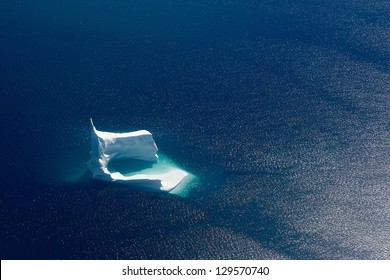Blue and white iceberg on deep blue background. Taken from a helicopter.