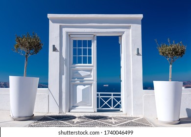 Blue and White Idyllic - White wooden door, gate or entrance to sea view on Santorini Island in Oia village, Greece. Welcome to a holiday resort