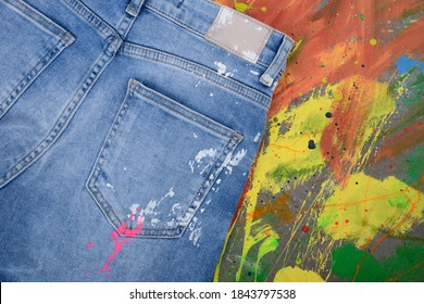 Blue and white Jeans isolated on splash colorful ink background back view
