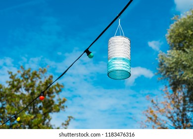 blue white lampion hanging on wire with lamps, against blue sky