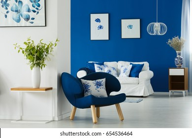 Blue and white living room decorated with flowers and flowery patterns