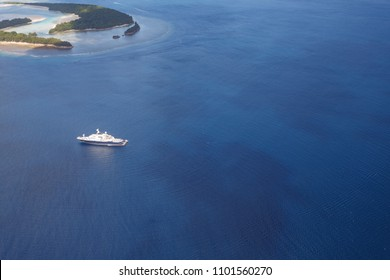 Blue and white mega yacht glides amid tropical islands in pacific waters