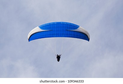 Blue and white para glider seemingly suspended against a light blue sky.