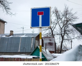 """blue white red big worn, battered, damaged, rusty road sign """"dead end"""", square mounted on a metal plate with bright reflective paint applied to attract attention in cloudy weather in residential area"""