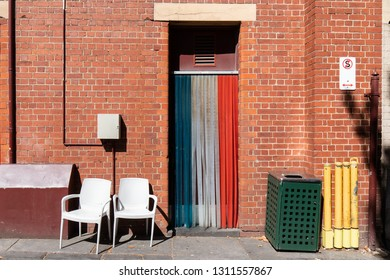 Blue, white, and red entrance surrounding by brick wall.