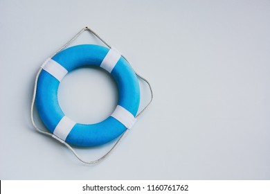 blue and white safety torus or lifebuoy hanging on white wall background, copy space