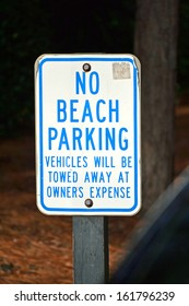 A blue and white sign that reads No Beach Parking