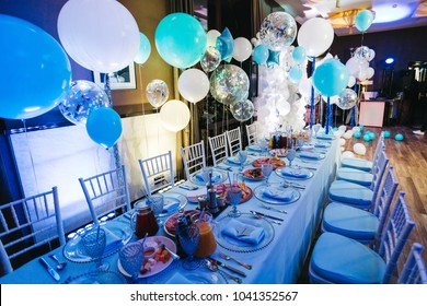 Blue white and silver balloons hang over blue dinner table in the dinner hall