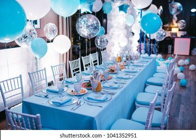 夕食会場の青いディナーテーブルの上に青い白と銀の風船が垂れ下がっている