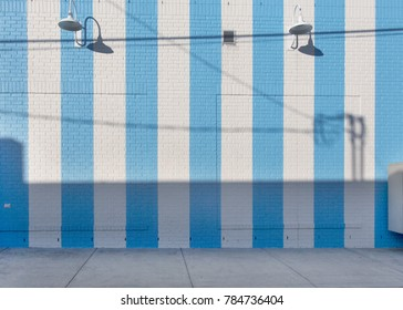 blue and white striped brick wall with lamps and sidewalk