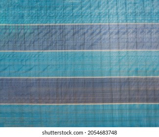 Blue and white striped plastic tarpaulin texture